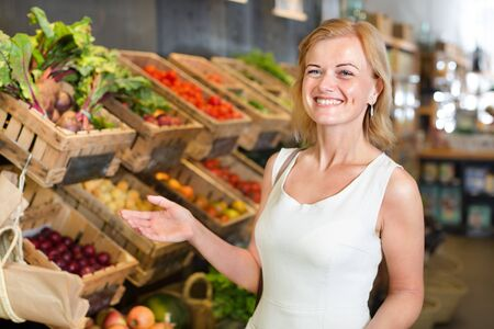 Glad young woman shopping various veggies and fruits at a food store