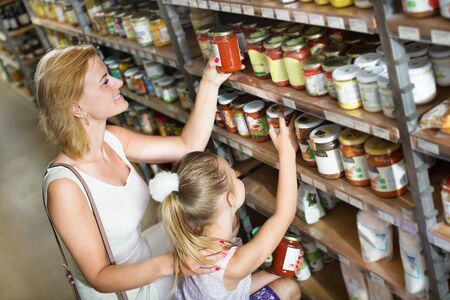 Glad young mother with daughter shopping conserve crushed tomatoes at the groceries