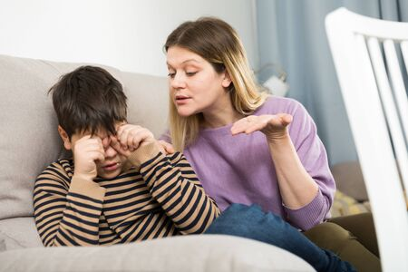 Upset mother and  offended son crying during  arguing in domestic interior