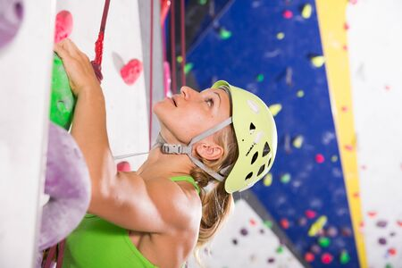 Female mountaineer climbing artificial rock wall with safety belts and helmet