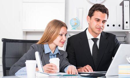 Geschäftsmann und Geschäftsfrau sitzen am Schreibtisch und arbeiten zusammen im Büro Standard-Bild