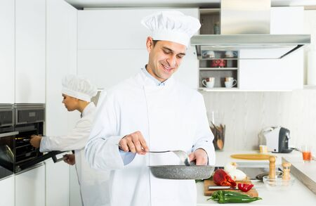Male cook wearing uniform with stewpot working on kitchen with woman cook