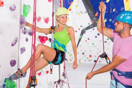 Female and male on joint workout in bouldering hall, climbing artificial rock wall with safety belts and helmet Stockfoto