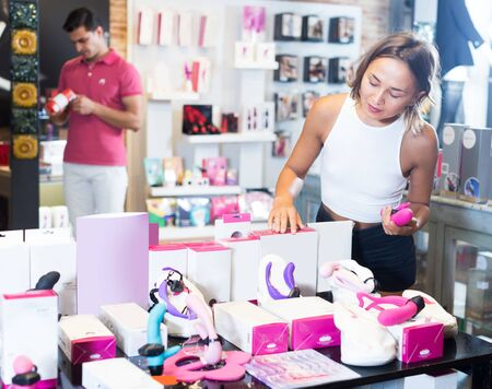 female buyer touching in the modern sex shop different sexy toys