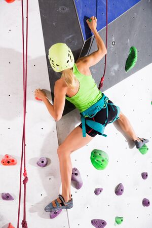 Sporty active woman dressed in rock climbing outfit training at bouldering gym