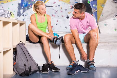 Athletic man and woman equipping for climbing workout at bouldering gym