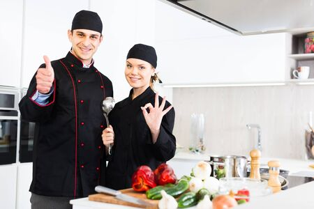 Man and woman young cooks wearing black uniform showing thumbs up on kitchen Foto de archivo