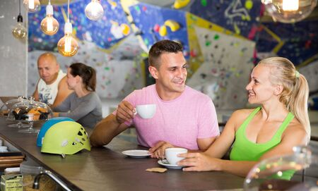 Portrait of happy athletic young people drinking coffee on break during indoor climbing workout