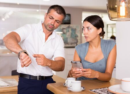 Annoyed man pointing at watch while his girlfriend absorbed in phone over cup of coffee in kitchen