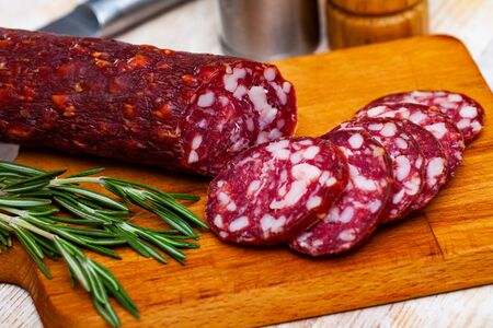 Traditional german thin semi-dry cured pork Braunschweiger sausage sliced on wooden cutting board with rosemary and spices