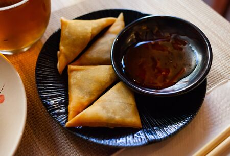 Potato curry samosas served with sause at plate, nobody Stock Photo
