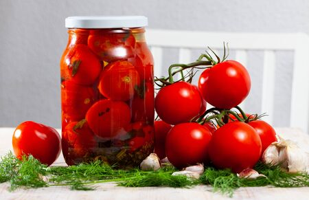 Jar with pickled tomatoes, dill, garlic and ripe tomatoes on the table Banco de Imagens