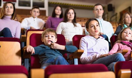 Group of cheerful positive people watching movie attentively in cinema Standard-Bild