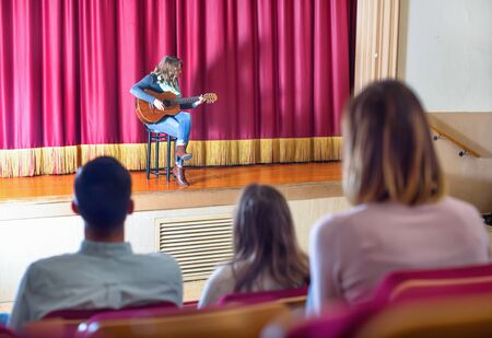 Large positive audience enjoying guitar concert in concert hall