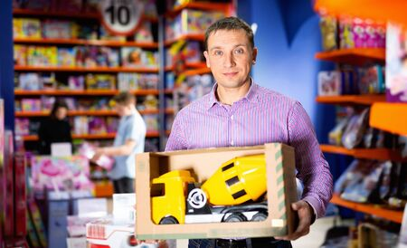 Portrait of cheerful positive adult man buying toy cement mixer machine in modern toy store