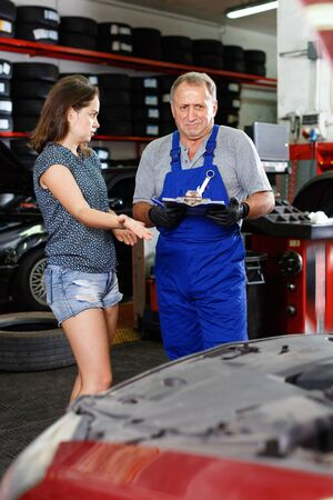 Unhappy young  woman displeased with repair of her car, conflicting with mature male mechanician at service station