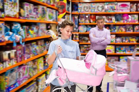 Teenage boy choosing doll stroller in modern toy store on background with surprised father