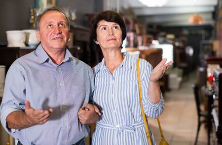 woman with her husband are buying furniture for home in antique store
