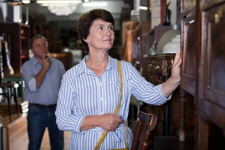 Mature woman is shopping the old buffet in the antique store.