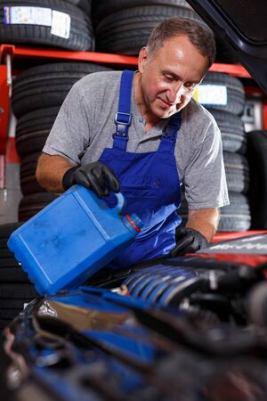 Mechanic technician checking and replacing motor oil in car at service station