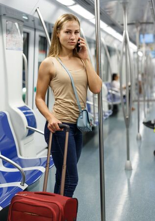 Young female traveler with luggage using mobile phone inside subway train Stock Photo