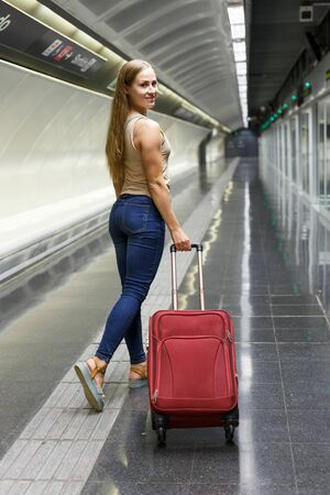Young woman with luggage waiting train in platform of subway station 免版税图像