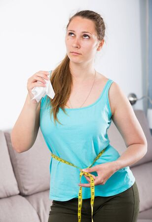 Young woman feeling distressed measuring her waist at home