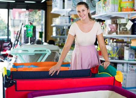 Smiling young pregnant woman choosing playpen for future baby in children mall