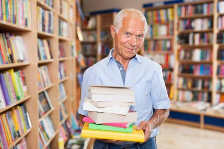 Smiling senior man holding pile of books bought in bookshop