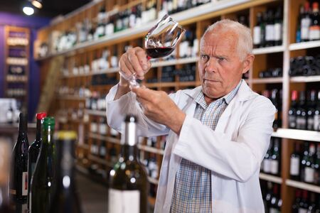 Confident elderly male winemaker holding glass of red wine, checking it in wine store