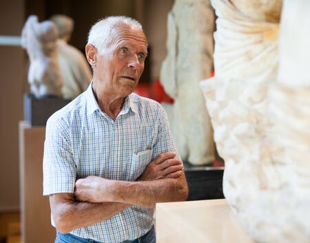 Mature Caucasian man visiting exposition of Art Museum with exhibits of antiquity Banque d'images