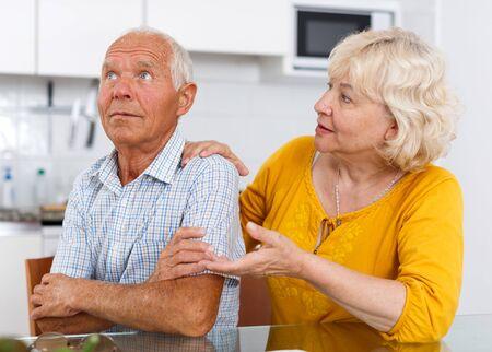 Portrait of unhappy mature couple discussion, quarrel at home interior