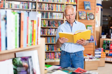 Focused efficient cheerful positive friendly man looking for information in books in bookstore