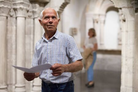 Male retiree visiting exposition of museum and reading guidebook
