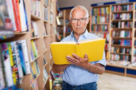 Focused satisfied  cheerful  elderly man looking for information in books in bookstore