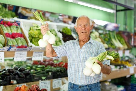 Elderly man looking for fresh organic vegetables in local market