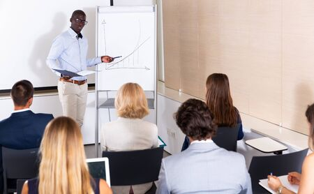 African American businessman making presentation on staff meeting at office
