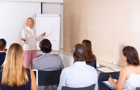 Successful mature woman sharing business ideas with colleagues in meeting room. Concept of teamwork