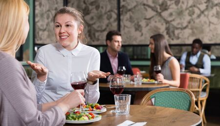 Happy smiling attractive girl emotionally discussing with female friend while dining in cozy restaurant Imagens