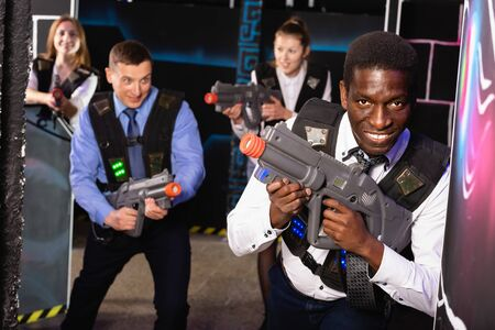 Group of satisfied pleasant  colleagues holding laser pistols playing laser tag game Banco de Imagens