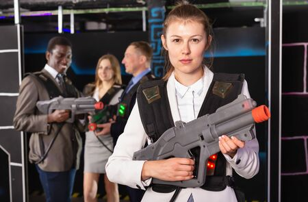 Woman in business suit holding the laser gun and playing laser tag with colleagues