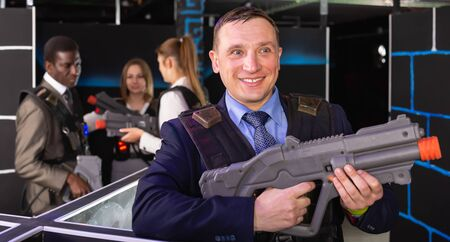 Adult man and his colleagues on background having corporative entertainment in laser tag room Banco de Imagens