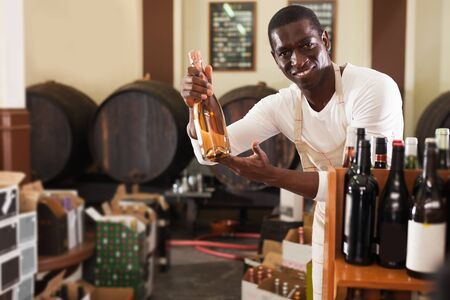 Portrait of cheerful smiling confident afro male seller of wine shop offering wine bottle to buy