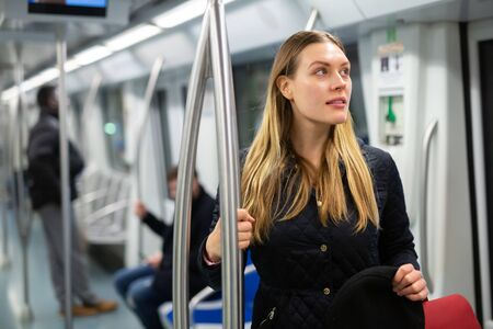 Portrait of smiling young woman holding on handrails during usual trip in subway car. Concept of daily city commuting