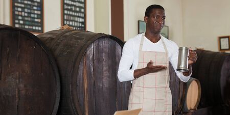 Positive African American male vintner proposing degustation of wine in modern winery