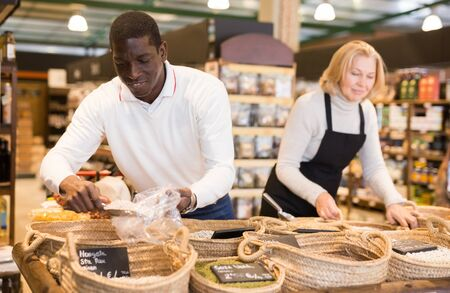 African American man making purchases in grocery store, filling polybag with groats