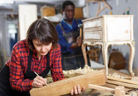 Woman and man carpenters using tools for restoration wooden bureau in studio