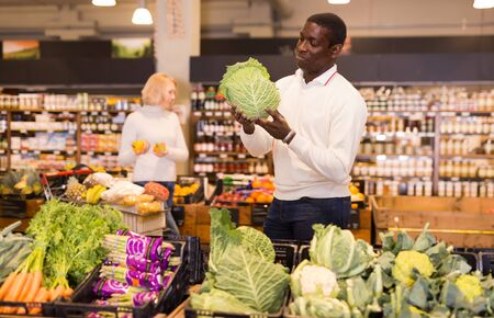 Adult African American man shopping in organic food store, choosing vegetables