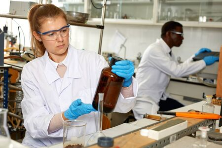Serious woman lab  scientist in glasses working with reagents and test tubes in laboratory Stock Photo