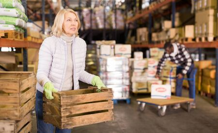 Focused mature woman working in store warehouse carrying empty wooden boxes